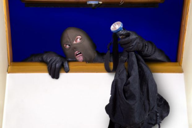 A masked person climbing through a window