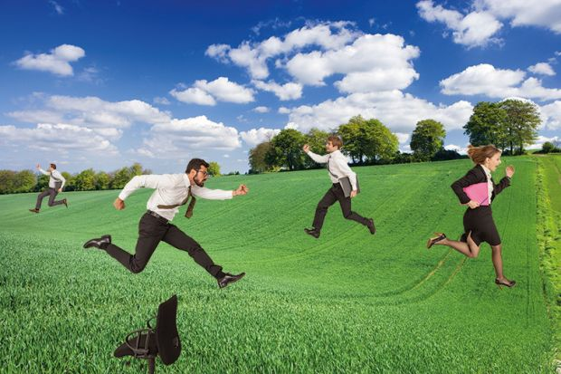Business people running through field
