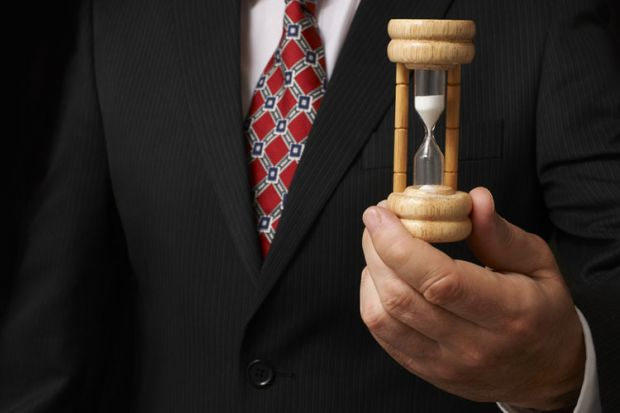 Businessman holding an egg timer