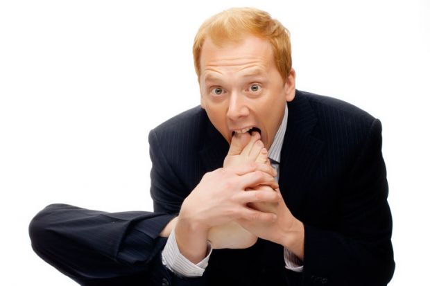 Businessman with foot in mouth