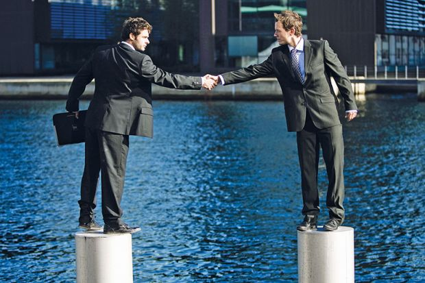 Businessmen shaking hands from pedestals in river