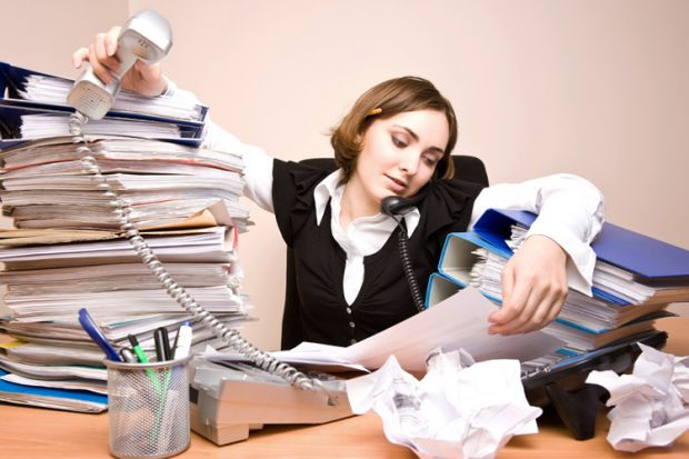 Businesswoman working at cluttered desk