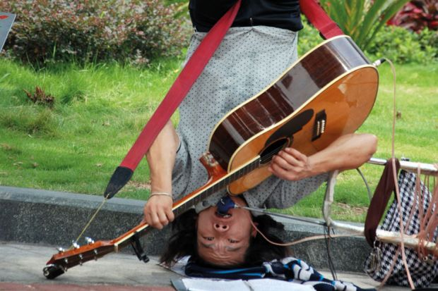Busker playing guitar upside-down
