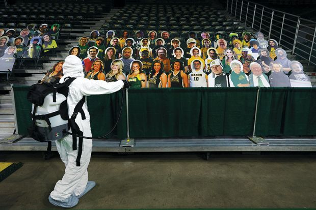 Man in PPE with audience of cardboard cut-out people, virtual conference, digital, remote