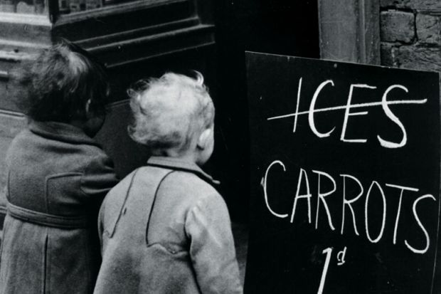 Small children looking at 'Carrots instead of ice lollies' sign