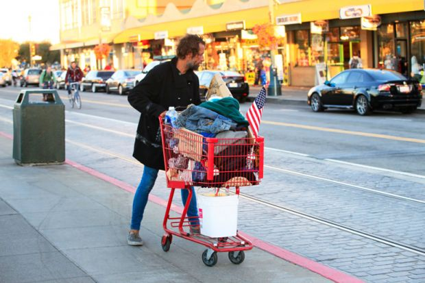 Homeless man pushing shopping cart full of belongings
