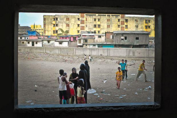 Children playing, viewed through open window, Dharavi, Mumbai