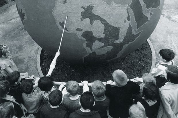Children viewing globe during geography lesson
