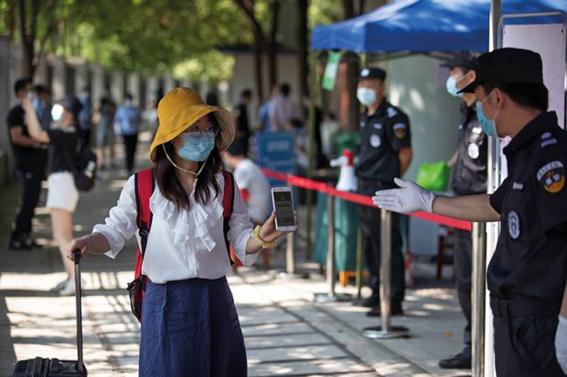 Student in mask shows mobile phone to health check in Wuhan, China