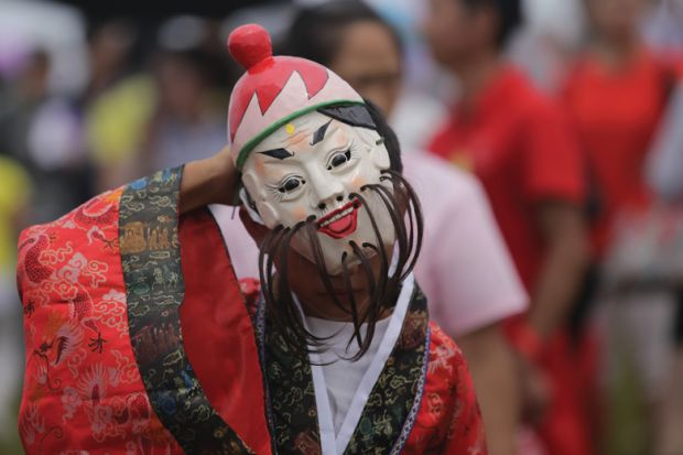 Chinese folk artist wearing mask performs
