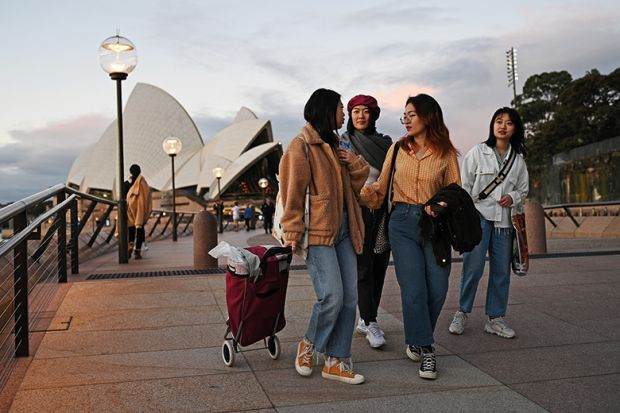 International students from China walk along the waterfront by the Sydney Opera House, after lockdown measures put in place to prevent the spread of the coronavirus outbreak were eased, June 2020. Will China pull the plug on Australian enrolments?