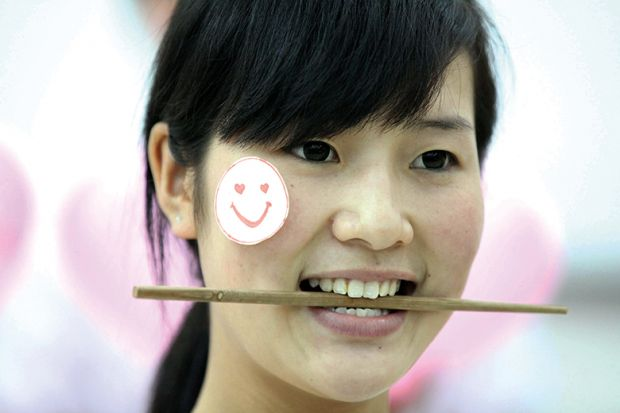 Woman with chopstick in her mouth