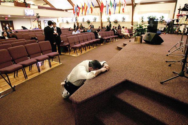 man prays in church