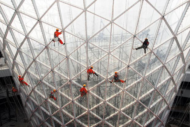Workers clean the exterior of the Sun Valley pavilion in Shanghai, China