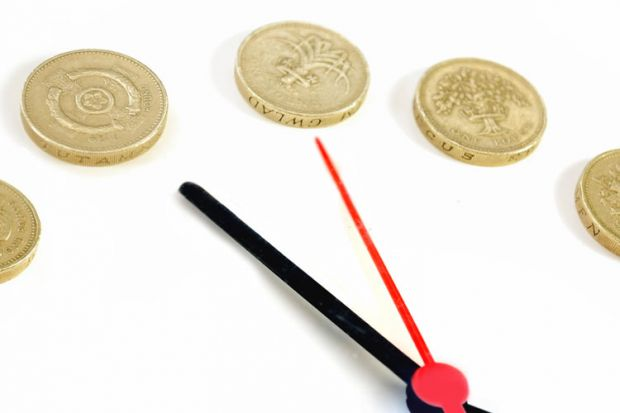 Clock hands and pound coins counting time