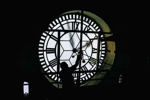 person fixing giant clock