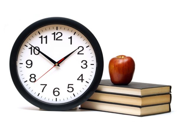 Clocks next to pile of books with apple