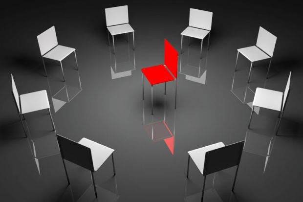 A circle of grey chairs with one red chair in the centre