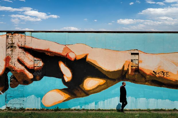Man walking past mural of clasped hands
