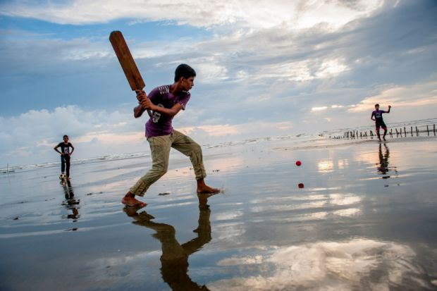 Boys play cricket on the beach