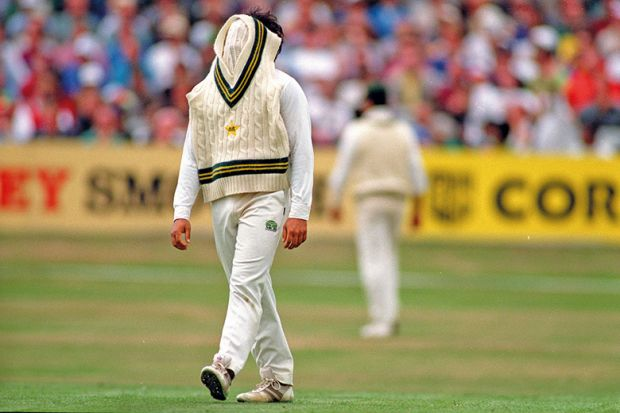 Cricketer with jumper over face