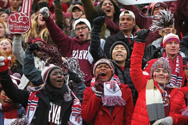 Crowd of Harvard University students cheering American football game