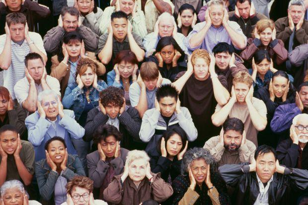 Crowd of people covering ears