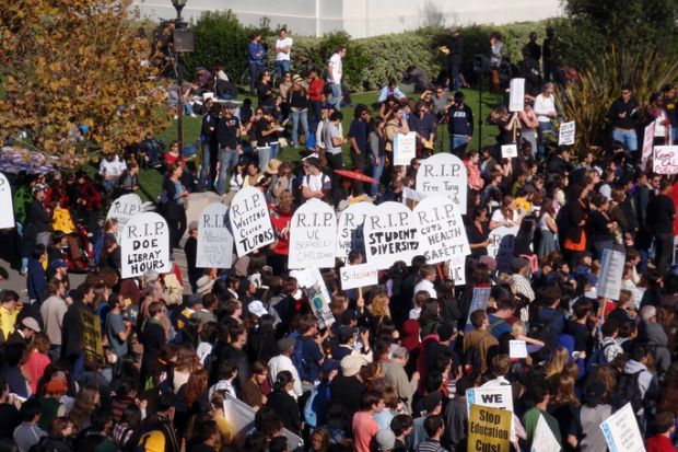 Crowd of protesters hold signs and rally tuition increases in front of Sproul Hall on UC Berkeley November 18 2009