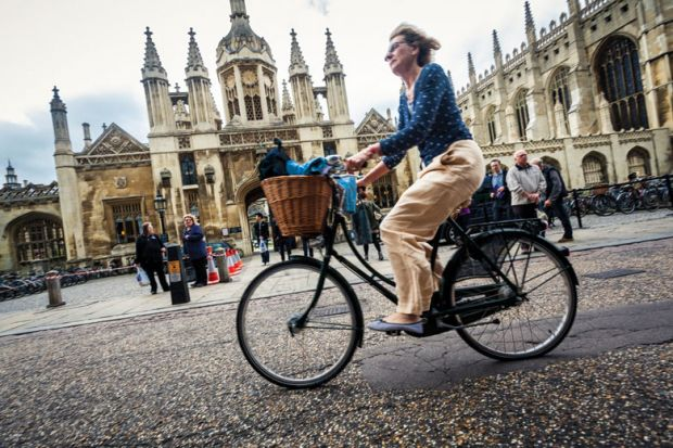 Cyclist outside University of Cambridge