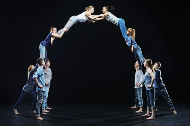 Dancers on stage forming human bridge