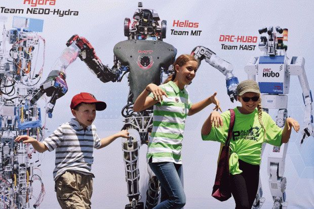 Children posing in front of picture of robots