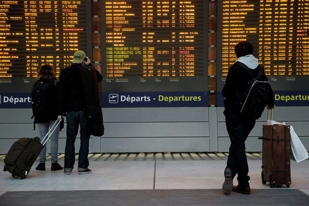 Passengers check departures board