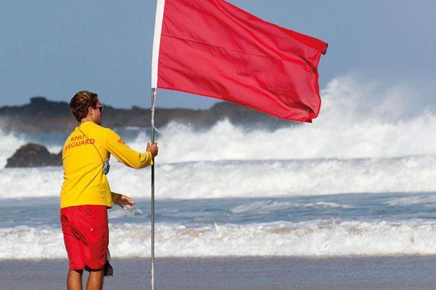 Man holding red flag on beach