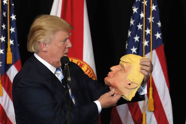 Donald Trump holding mask of his own face