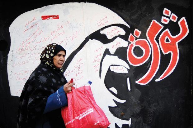 Egyptian woman walks past 'Revolution' graffiti, American University in Cairo