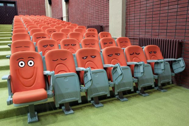 Emotive faces drawn on lecture hall chairs