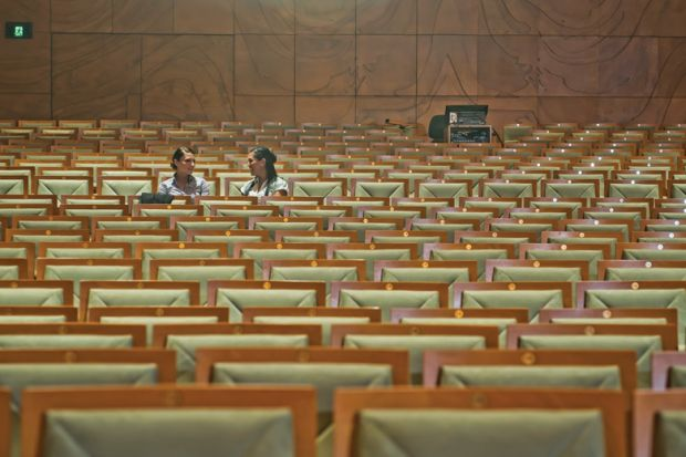 Two women in empty lecture hall