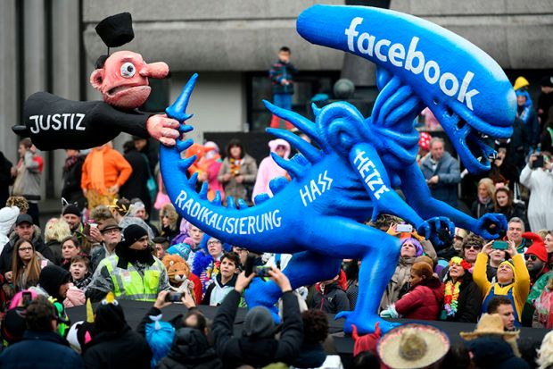 A carnival float depicting a judge holding the tail of an alien whereupon is written 'radicalisation, hate, rush, Facebook' in Germany 2020. To illustrate whether scholars on Facebook's oversight board are helping rule on moderation rows.