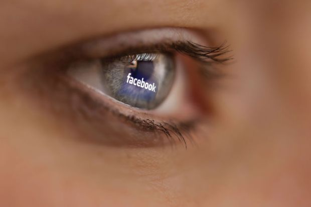 Reflection of Facebook logo on person's eye