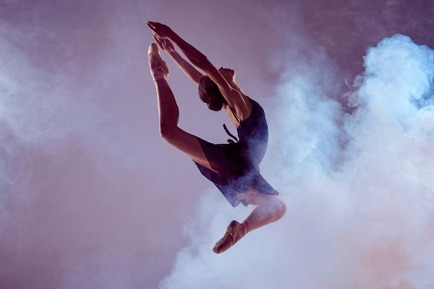Female ballet dancer jumping through dry ice