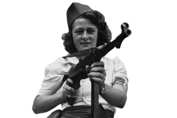 Female French Resistance fighter holding machine gun