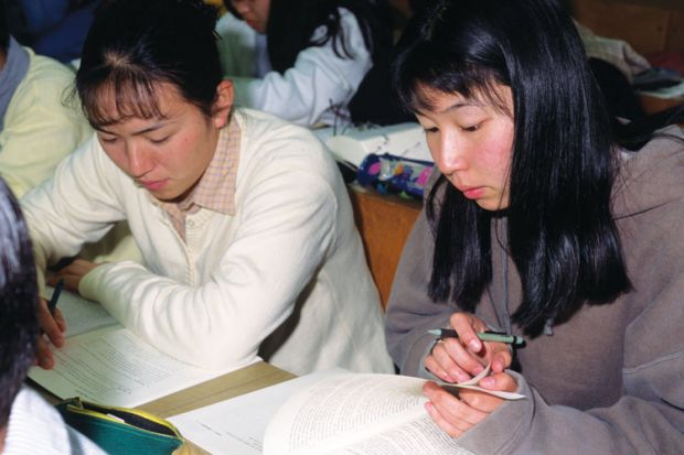 Female Japanese students reading textbooks
