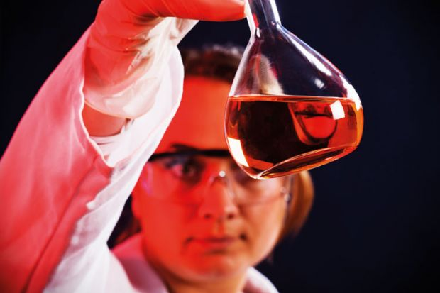 Female scientist examining flask of liquid