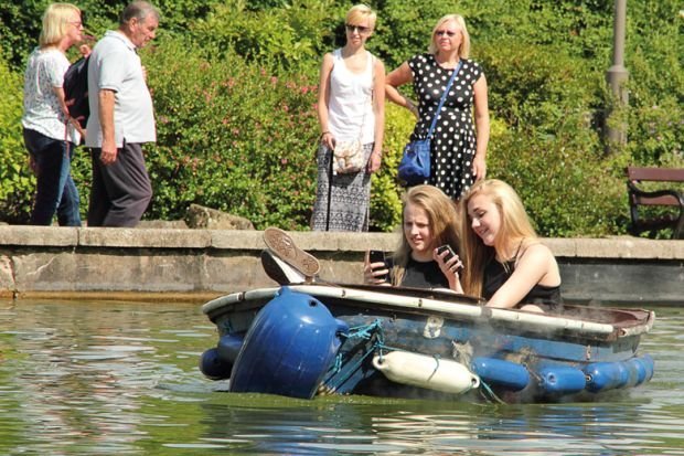 Female students using smartphones on boating lake