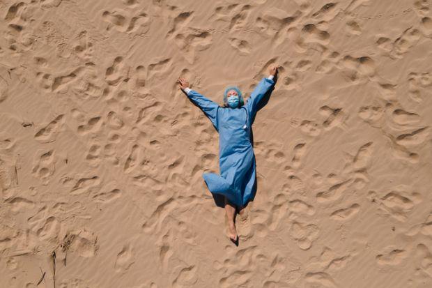 female doctor in medical gear lying on sandy beach