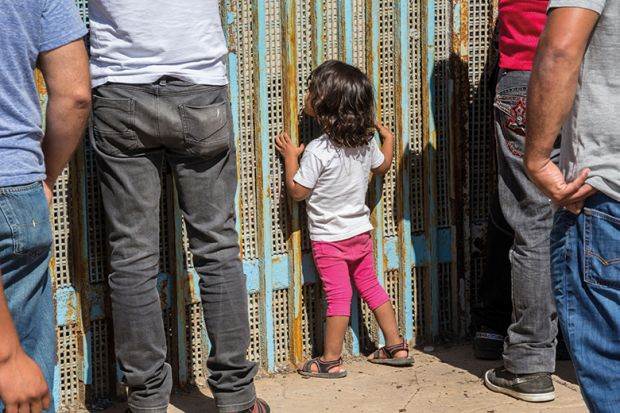 people stand at a fence