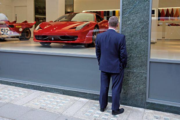 Man window shopping at Ferrari showroom