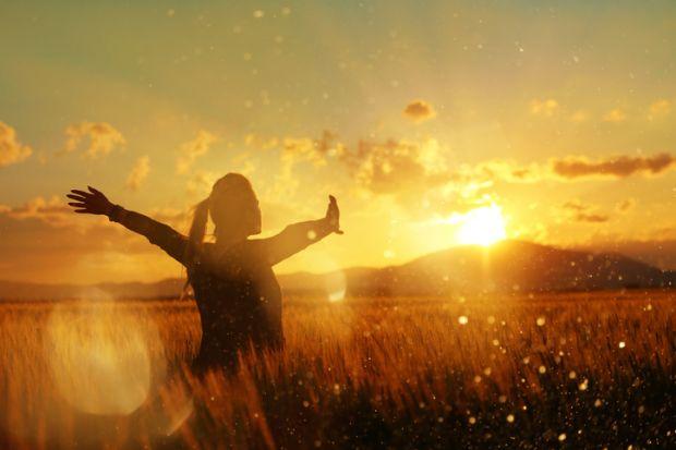 A woman in a wheatfield at sundown