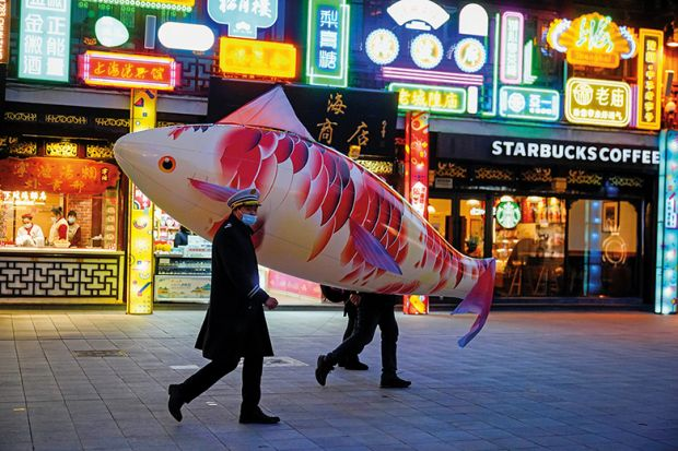 Security guards wearing face masks carry a giant balloon in the shape of a fish in Shanghai