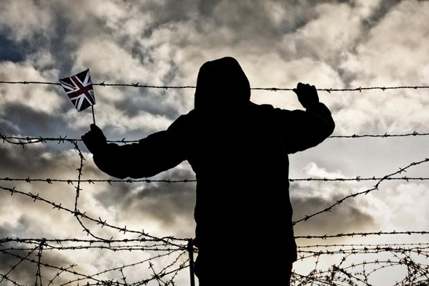 Silhouetted figure holds Union Jack